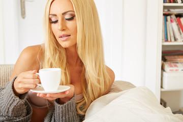 junge blonde frau trinkt kaffee auf der couch