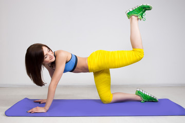 happy cutie athletic girl ,  execute exercise on muscles belly