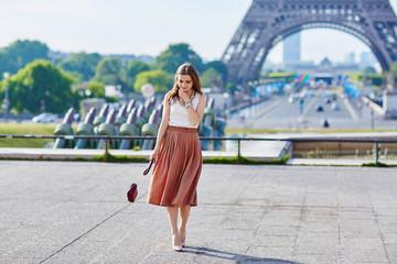 Beautiful young Parisian woman near the Eiffel tower Wall mural