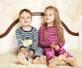 boy and girl in pajamas on bed