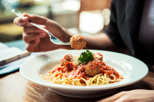 close up of woman eating spaghetti meatball