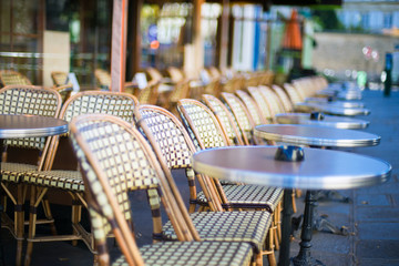 Empty tables between dining hours along Paris cobblestone alley way