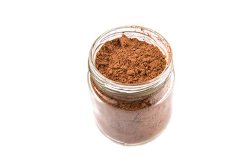 Brown pure cocoa powder in a mason jar over white background