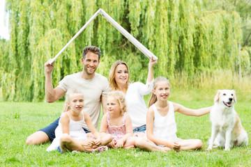 Familie unter einem Dach im Grünen
