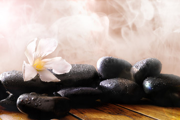 Group of black stones on wood base with steam background