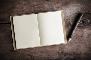 Open blank notebook on wooden table, Vintage tone
