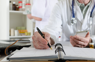Doctor holding a smartphone and taking notes