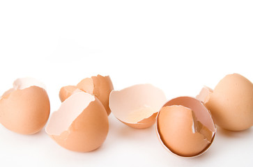 Brown Chicken Eggshells – Cracked open brown egg shells from a chicken. On a white background.