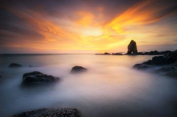 Sea wave hit the rock at sunset in Thailand