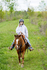 Young Horseback Rider – A young girl rides a horse in the country.