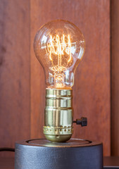 Vintage edison light bulb with wood background for hotel decorat