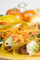 Beef Tacos Plate – Ground beef tacos on a plate, with lettuce, sour cream, cheese, and tomatoes.