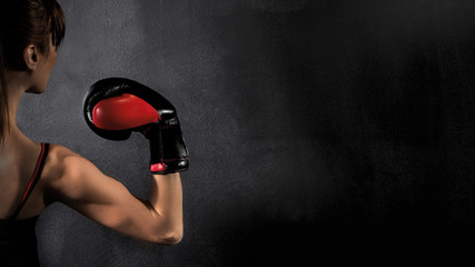 Woman Boxer Biceps with Red Boxing Glove on Black Background, high contrast with saturated grunge filter