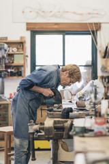 Woman senior artist cutting wood in a workshop