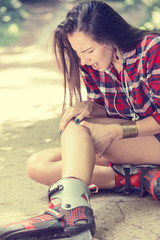 injured young woman suffering from pain sitting on the ground