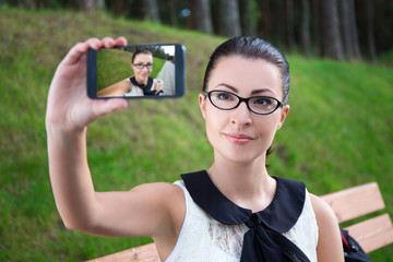 happy beautiful girl making selfie photo on mobile phone