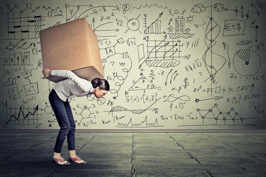 woman carrying heavy box walking along gray wall