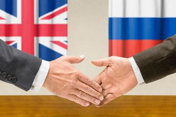 Vertreter Großbritanniens und Russlands reichen sich die Hand