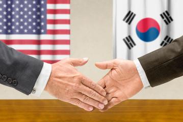 Vertreter der USA und Südkoreas reichen sich die Hand