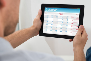 Person With Digital Tablet Showing Calendar