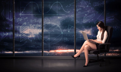 Businesswoman holding laptop in office room with graph charts on