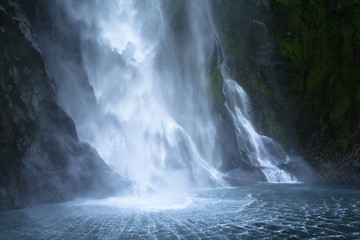 Wall Murals Waterfalls A waterfall in Milford sound , New Zealand