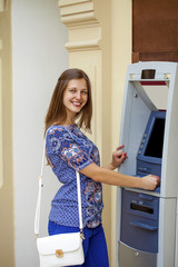 Smiling young woman withdrawing money from ATM