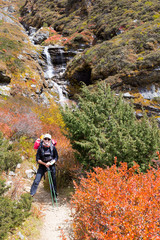 Wall Mural - Young happy woman backpacker standing mountain waterfall.