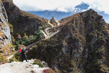 Fototapete - Woman backpacker standing mountain trail near buddhist stupa.