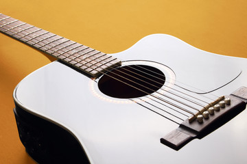 Black acoustic guitar on yellow background, with light reflection