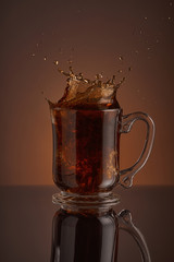 Splash of black ice coffee, refreshing drink on a brown background. Liquid drink pouring into a cup with ice. Pour high speed beverage for promoting restaurant, bistro and bar.