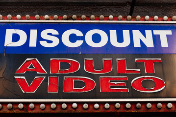 "Discount Adult Video. Worn down sign reading ""Discount Adult Video"" along an urban city downtown street."