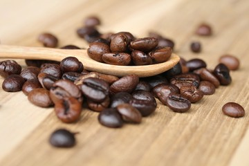 Coffee beans in wooden spoon, close up