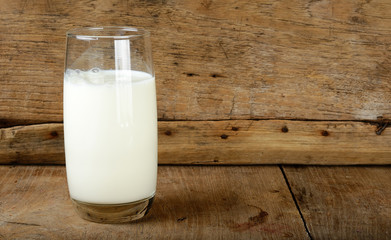Glass with milk on the wooden background
