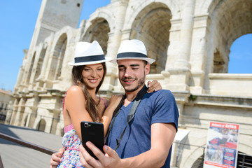 Fototapeta cheerful young couple of tourist visiting europe and making a selfie in front of a famous monument