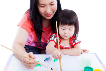 Mother with child girl draw and paint together. On white