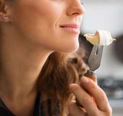 Closeup of woman's mouth getting ready to eat piece of Camembert