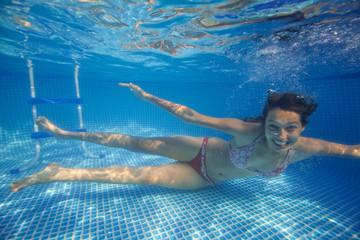 Underwater woman in swimming pool.