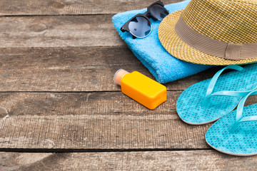 Summer beach essentials on old wooden background