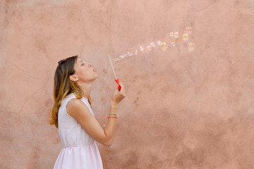 Girl blowing soap bubbles against colourful backdrop