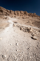 Valley of the Kings path and tombs. A view along a narrow path leading up the limestone cliffs towards openings in the cliffs which identify tomb entrances.