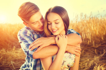 Happy couple kissing and hugging outdoors on wheat field, love concept