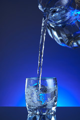 Jug water poured into a glass, splash, blue background, refreshing, freshness and health. Water bottle, water pitcher, blue liquid, ice, drops, motion, wave, splash, transparent blue water,