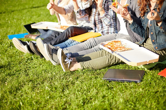 close up of teenage students eating pizza on grass