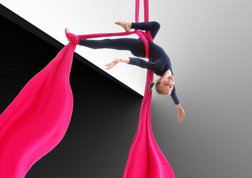child hanging upside down on aerial silks
