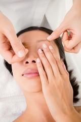 Hands threading beautiful womans eyebrow