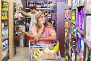 Pretty young woman looking at shelf