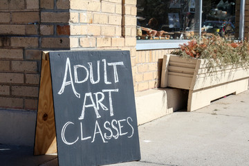 Adult Art Classes sandwich board outside a building