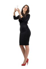 Elegant business woman in black dress talking selfie with cellphone isolated