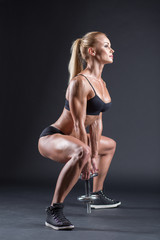 Portrait of a beautiful girl athlete with a dumbbell in studio